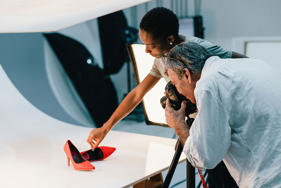 Two photographers taking a product photo of some bright red high heels